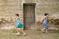 Girls running from wooden door