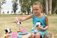 Girl having a tea party with soft toys