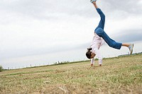 Girl doing a cartwheel in a field