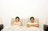 Couple in bed ignoring each other