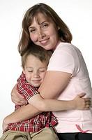 Mother hugging son (4-5) in studio