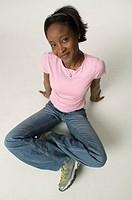 Teenage girl (13-14) sitting on floor in studio, portrait, elevated view