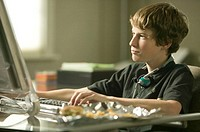 Boy sitting at table, using computer, close-up