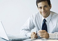 Businessman sitting at desk next to laptop, smiling at camera