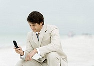Businessman using cell phone on the beach