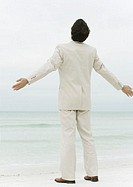 Businessman standing on beach with arms out, rear view