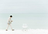 Businessman walking on beach