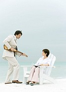 On beach, man in suit serenading woman sitting in deck chair