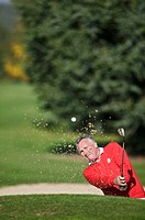 Man playing golf, ball in air