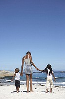 Woman walking on beach holding hands with two daughters (4-6)