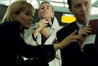 Businessman shaving in queue at airport check-in desk