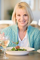 Mature woman eating salad, smiling, portrait