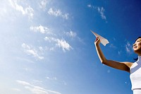 Young woman throwing paper airplane, smiling, low angle view