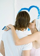 Woman holding paint brush, kissing man, heart painted on wall in background