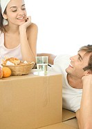 Couple having breakfast on cardboard box