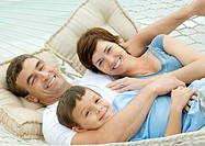 Family lying in hammock, smiling