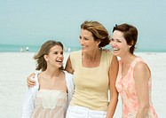 Three generations of women on beach, smiling