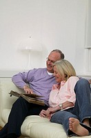 Mature couple relaxing on sofa looking at photo album, smiling
