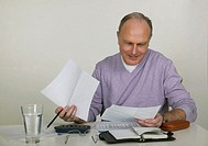 Mature man sitting at desk looking at bills, smiling