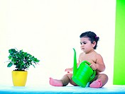 Toddler with watering can and indoor plant
