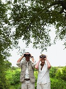 Mature couple on safari, standing under tree using binoculars, smiling