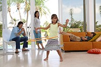 Girl (7-9) playing with hoop in living room, family in background