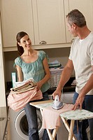 Couple in kitchen, man ironing, woman holding finished pile