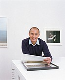 Man in art gallery holding  print, smiling, portrait