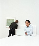 Woman in art gallery using laptop, man hanging picture in background