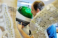 Advanced spacesuit. Researcher adjusts the helmet of a BioSuit. This is a prototype advanced spacesuit designed by Dava Newman, professor of aeronauti...