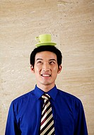 Businessman balancing cup on his head