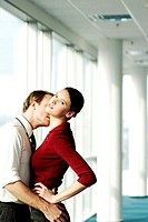 Two executives kissing in office corridor