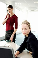Businesswoman using laptop while her colleague talking on the phone