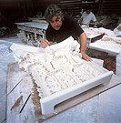 Plasterwork. Sculpturer working on a piece of plasterwork.