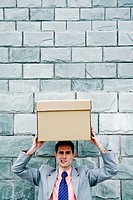 Businessman carrying a box on his head
