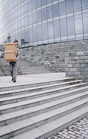 Businessman carrying a stack of boxes down the stairs