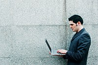 Businessman standing while using laptop
