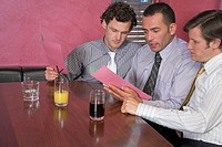three men sitting in restaurant reading menu together