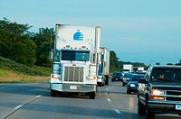 Semi tractor/trailers transporting goods on freeway, sharing road with passenger vehicles