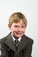 Young blond boy, wearing a suit, posing for the camera