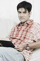 Portrait of a young man with a book on his lap listening to an MP3 player