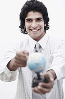 Portrait of a businessman pointing to a globe