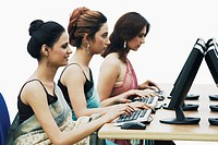 Side profile of three businesswomen working on computers in an office