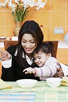 Close-up of a mother with her daughter at the dining table