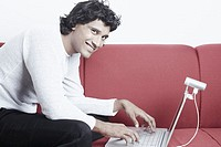 Portrait of a young man sitting on a couch in front of a laptop