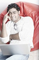 Young man sitting on a bean bag in front of a laptop