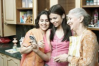 Three women standing in the kitchen and looking at a mobile phone