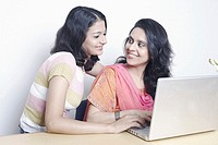 Mid adult woman and a young woman in front of a laptop