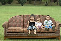 Three children sitting on a couch outdoors