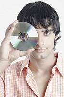 Portrait of a young man holding a compact disk in front of his face